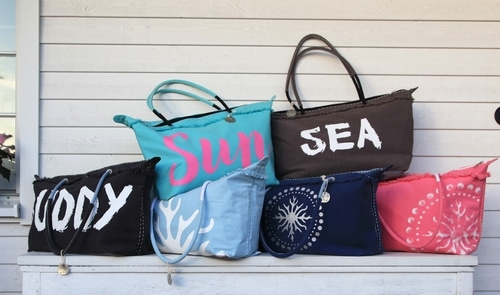 Stack of beach bags with words and designs on them