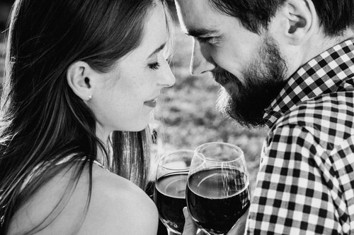 Black and white photo of a couple staring at each other in the eyes while drinking wine