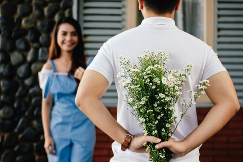 Man about to surprise his girlfriend with a bouquet of flowers