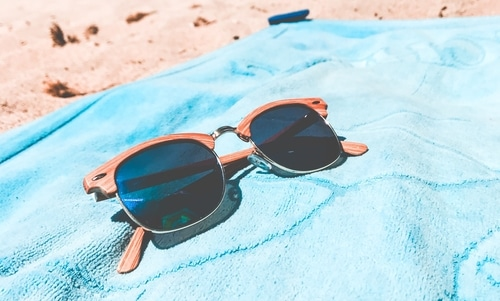 Wooden sunglasses on blue towel at the beach