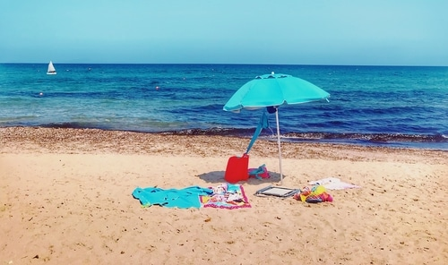 Blue umbrella covering items at the beach