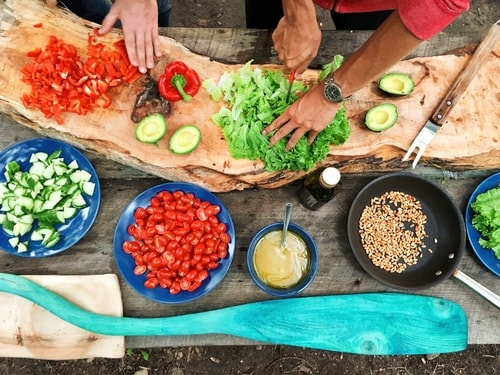Couple cooking with ingredients spread out at home