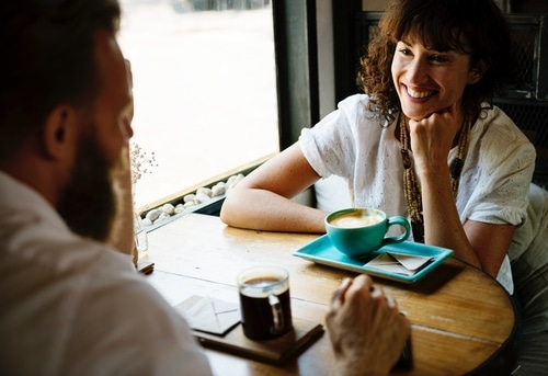 Couple smiling and talking at table while drinking coffee