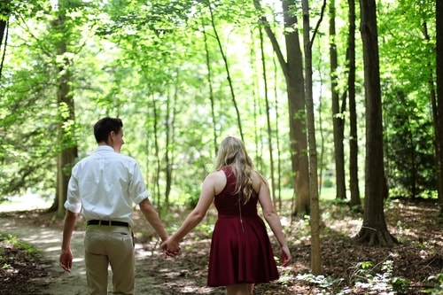 Couple walking through a trail in the wood together while holding hands