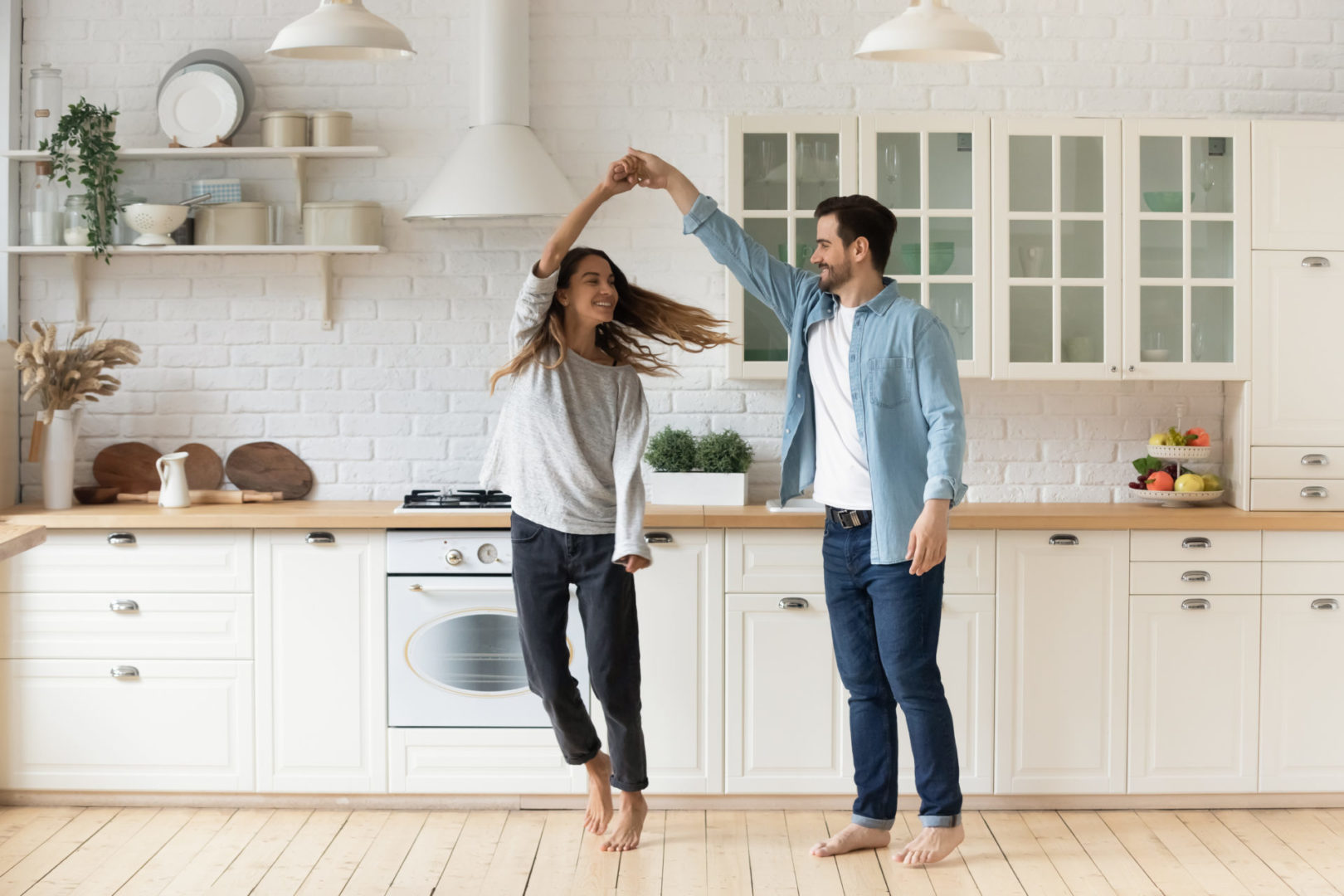Happy loving couple having fun in kitchen, dancing together, celebrating relocation or anniversary, handsome young husband holding beautiful wife hand, moving to favorite music, enjoying date