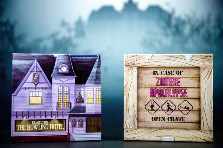 Photo of two date night boxes. The Date night boxes are escape from the howling hotel, an escape room date night box, and a zombie apocalypse themed date night box. They are set in front of a spooky hazy back drop.