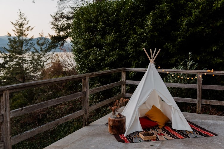A Sweet little teepee with pillows and blankets overlooking a mountain-scape lake view.
