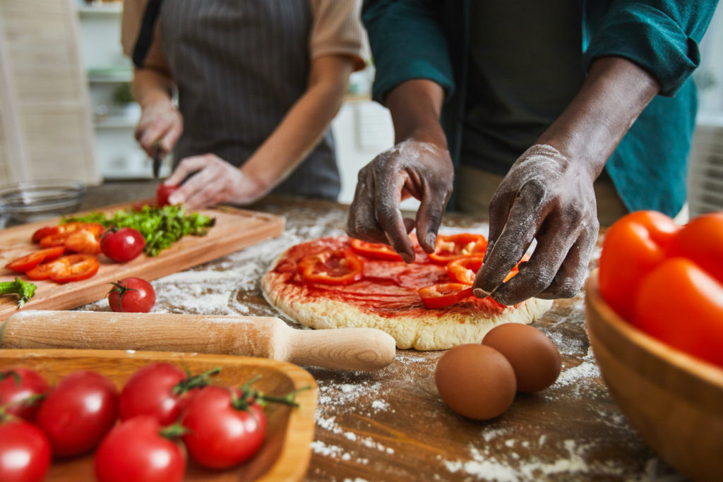 Close-up of man putting pepper on dough for future pizza with woman cutting vegetables in the background