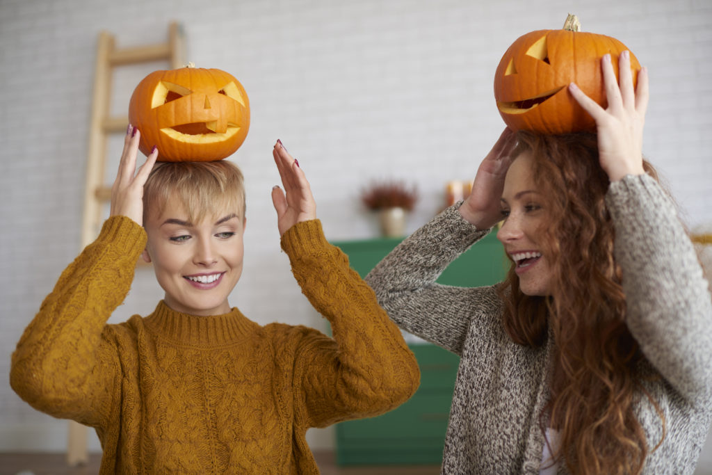 Girls having fun with halloween pumpkins places on their heads. they are smiling.