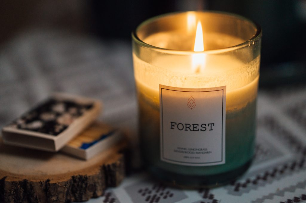 A Forest scented candle lit on a table by match boxes.