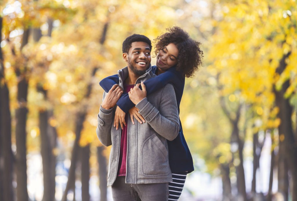 Happy lovely African American couple spending time at fall park, girl hugging guy from behind