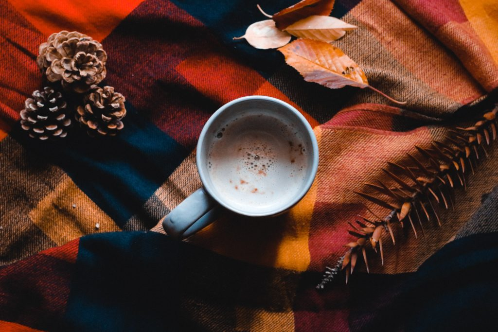 A hot mug of hot coco on top of a autumn colored blanket.
