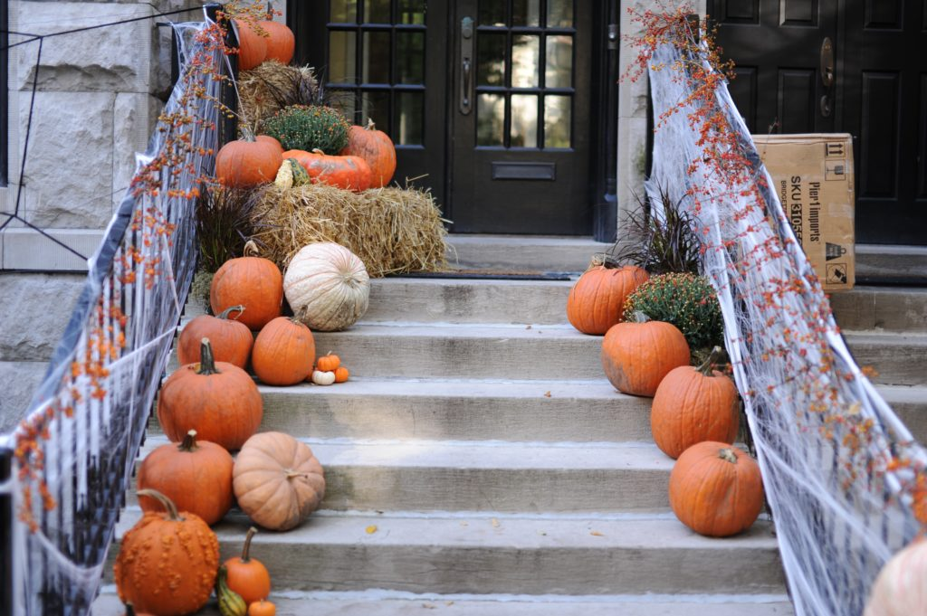 a entry way of a home where the stairs up to the door are festively decorated with Halloween décor, spider webs, and pumpkins of all shapes and  sizes.