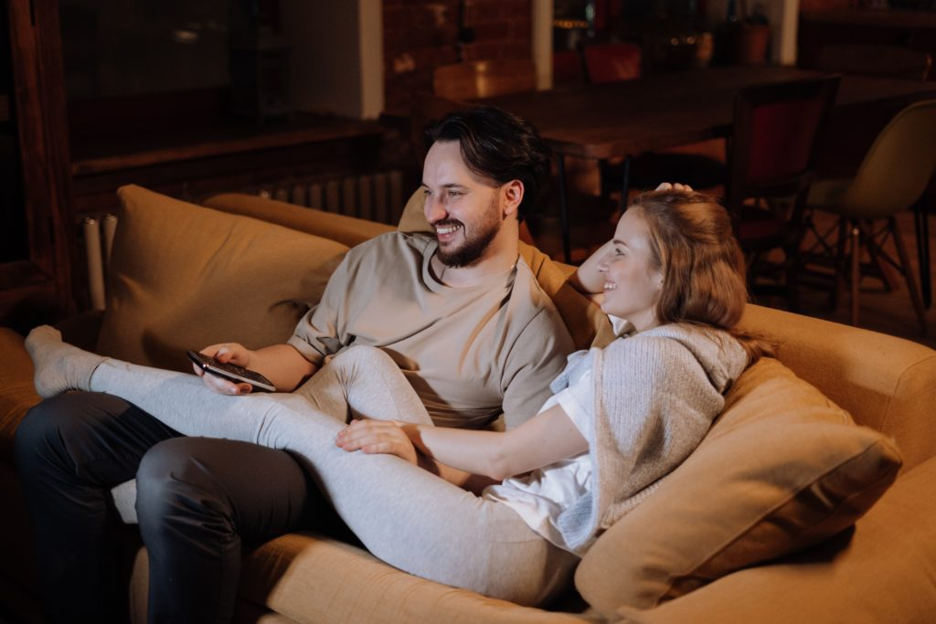 A Couple smiling as they sit on the couch watching television