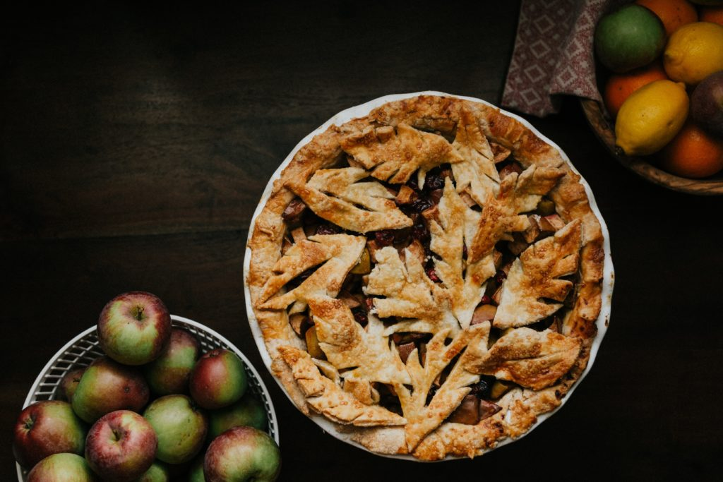 A Beautiful freshly baked apple pie sitting on a counter top. Bowls of fruit surrounding, this pie is covered in intricately designed leaf shaped golden brown pie crust.