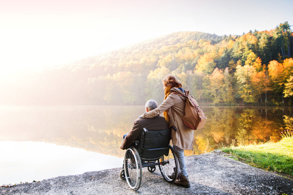 Active couple on a walk in a beautiful autumn nature. A woman and man in a wheelchair by the lake in the early morning.