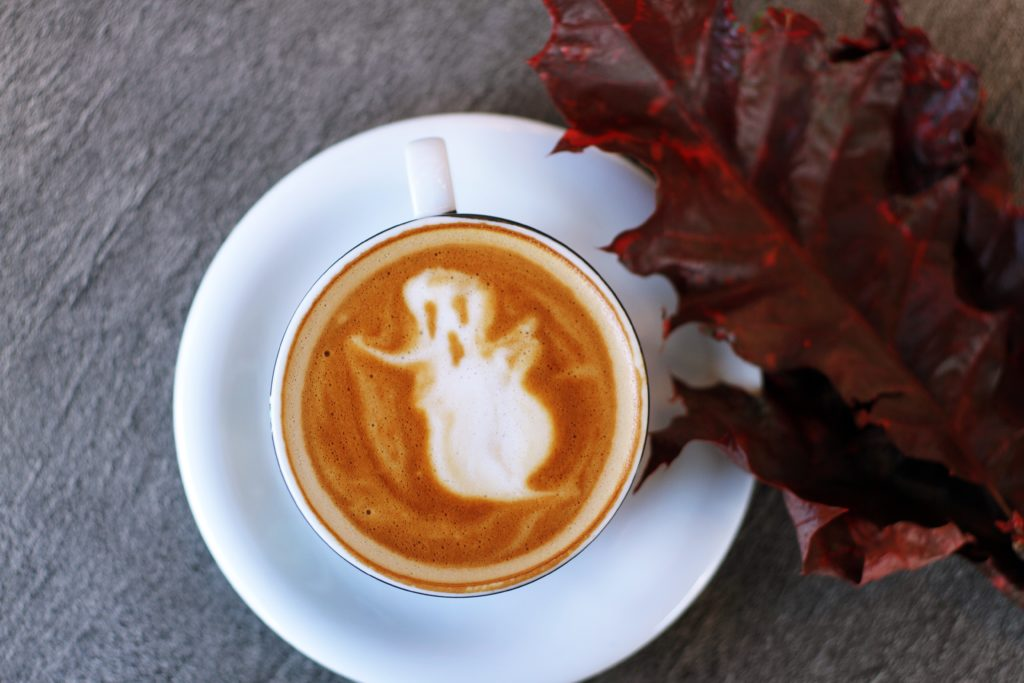 a ghoulish ghostly figure in latte art, placed on a table surrounded by leaves.